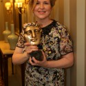 Me, dressed up, holding a BAFTA in a hallway outside the Style Suits at the Savoy Hotel