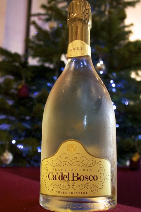 A bottle of Ca' del Bosco Cuvee Prestige in front of a Christmas tree